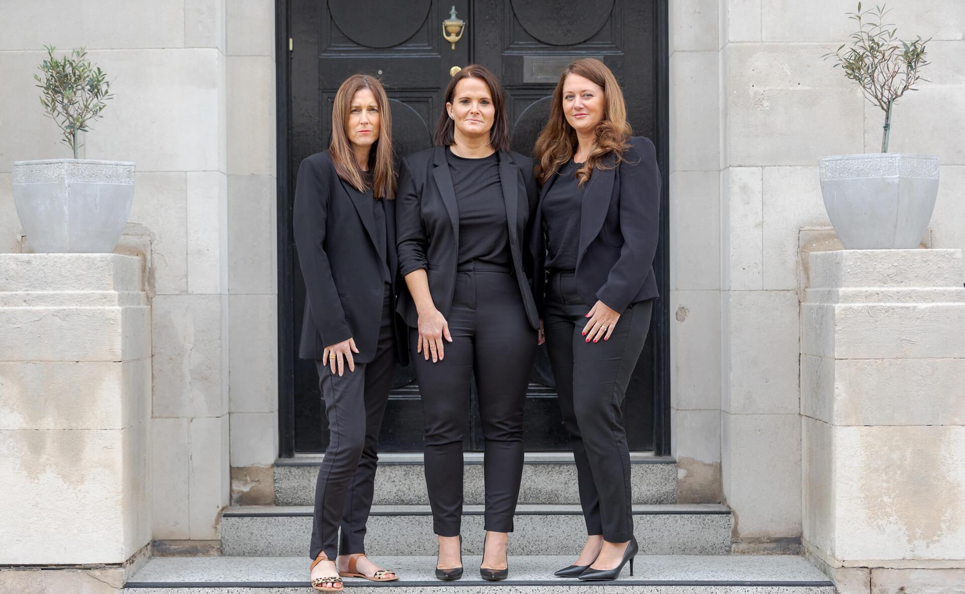 3 women standing aside each other in front of a door