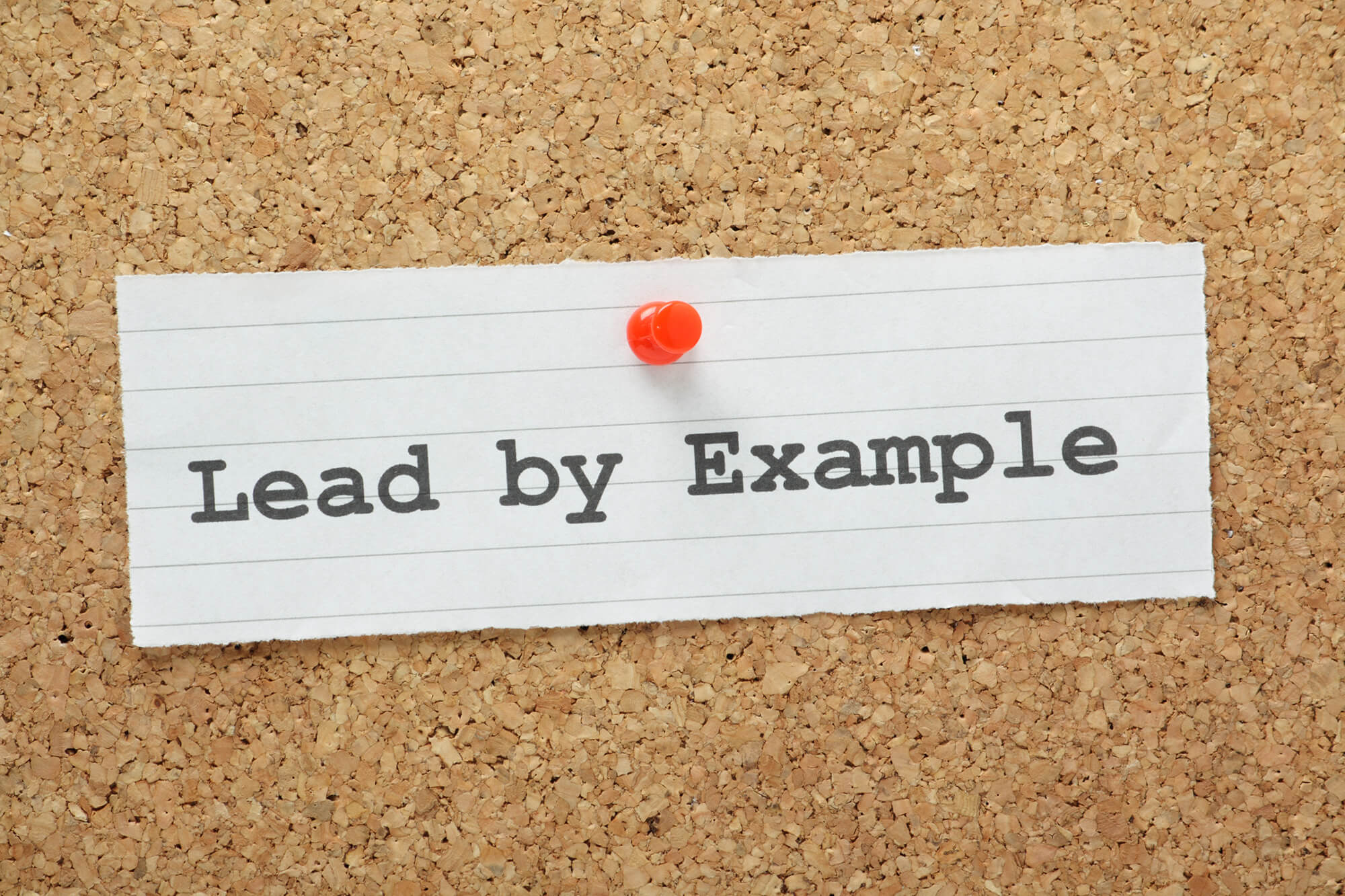"""lead by example"" written on a paper stamped against a wall"