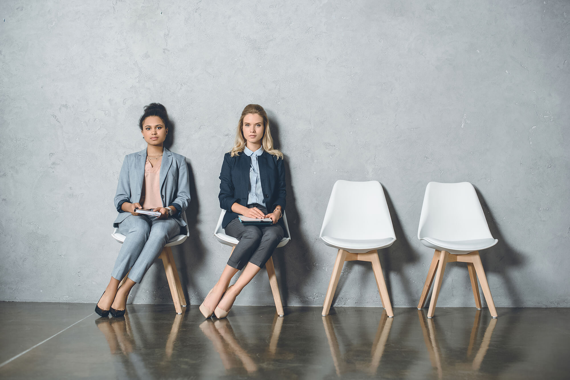 Two women sitting on a two chair waiting for something