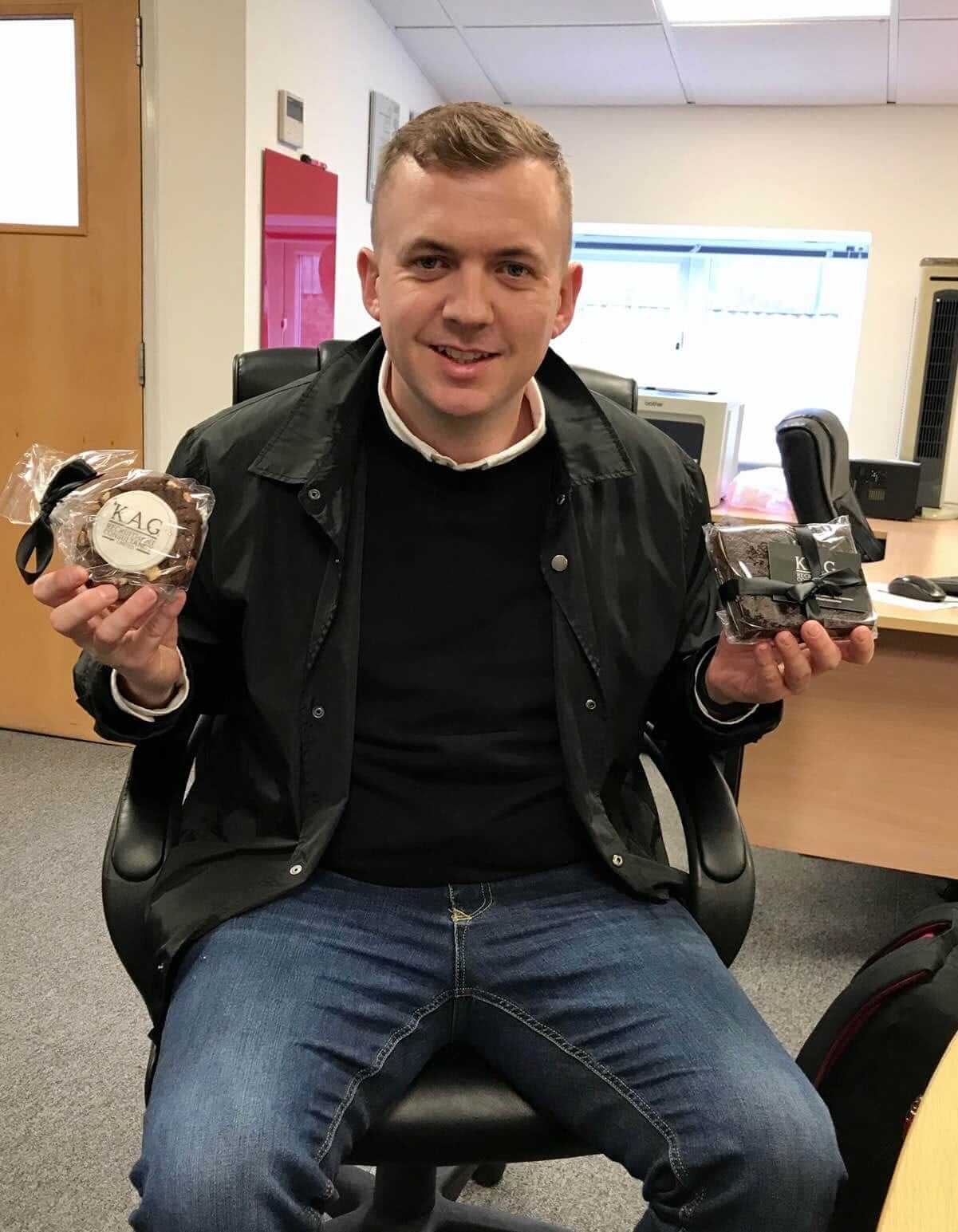 a man wearing black shirt and black jacket and holding chocolates in both hands