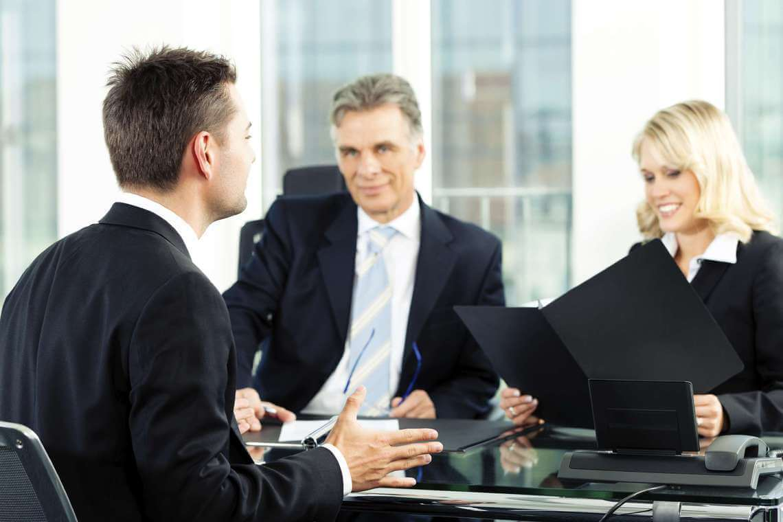 a man being interviewed with a panel of interviewers