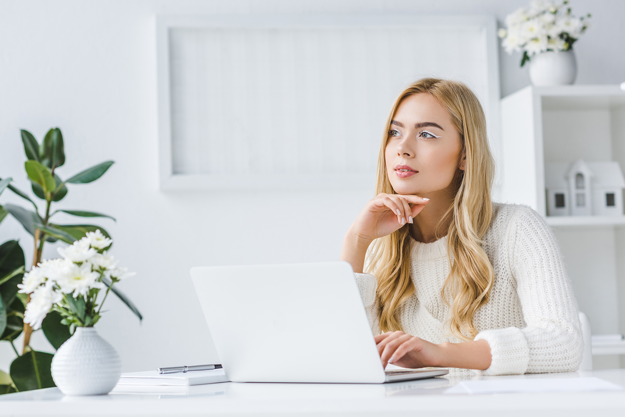 woman on laptop in white room